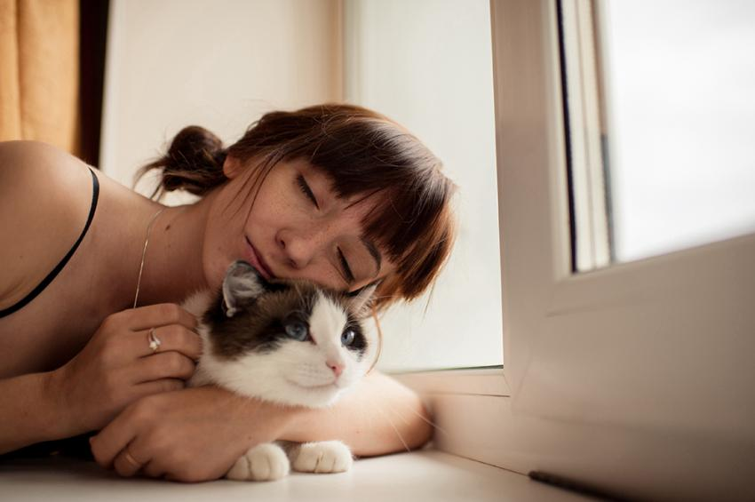 Woman snuggling with a black and white cat