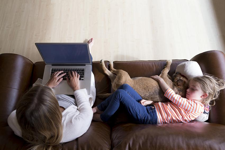 Family on couch with dog shopping for pet products