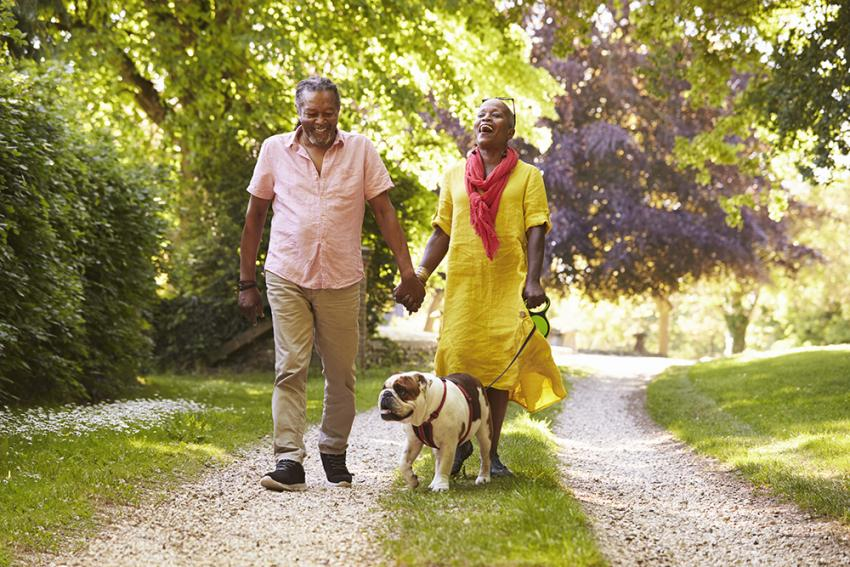 Couple walking a dog on a wooded trail