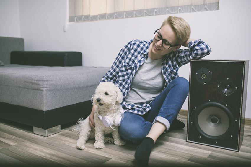 Dog and pet parent listening to music in front of speaker