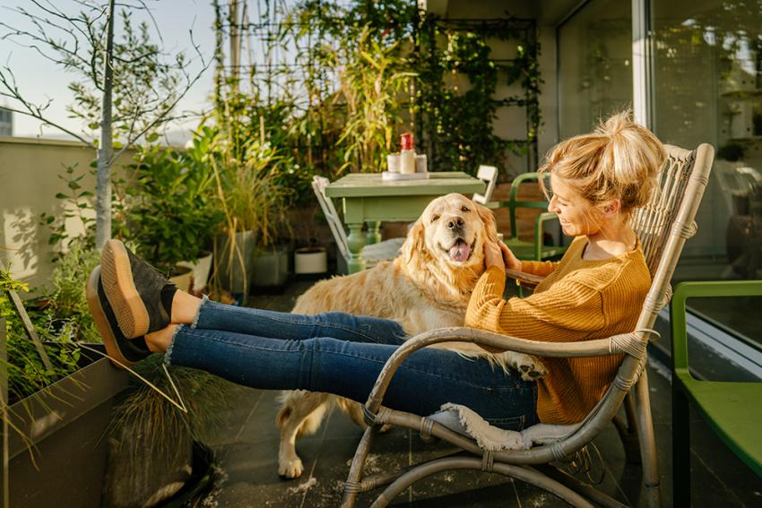Woman sitting on balcony with a dog