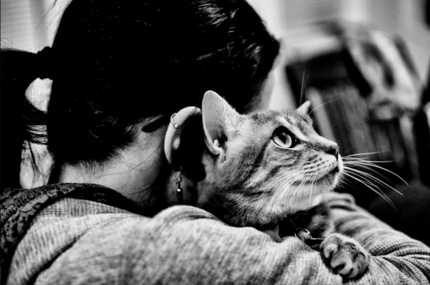 Photo of a woman with a cat on her shoulder by Ray Skwire.