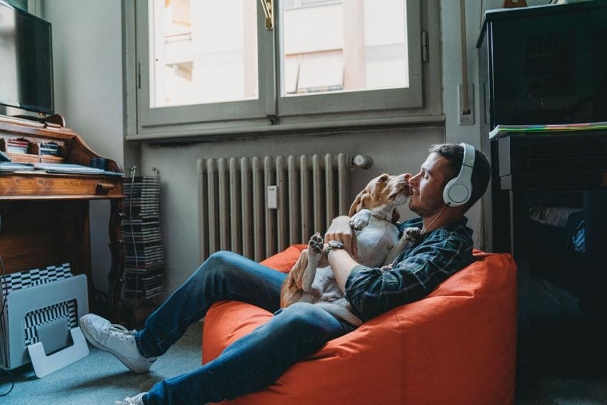 Man listening to music with his dog in a bean bag chair