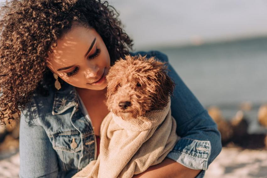 Woman hugging her small dog on beach