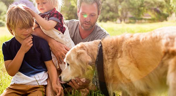 Family playing outside with dog