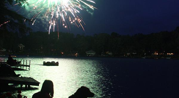 Girl and dog watching fireworks over lake
