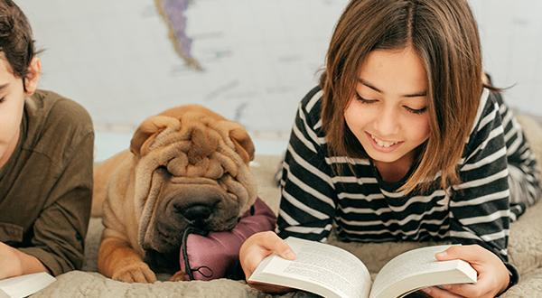 Children reading school books on bed next to dog