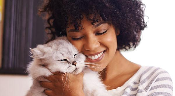 woman hugging her white cat affectionately