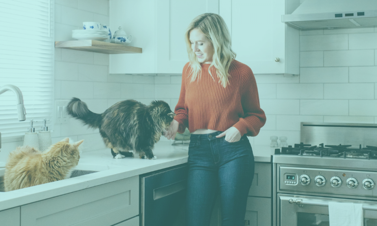 Woman stands in kitchen with her two cats